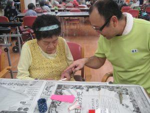 スタッフと利用者が紙を切る。