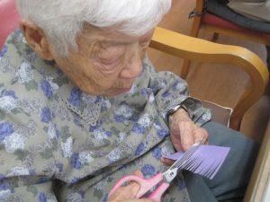 利用者がハサミで紙を切る。